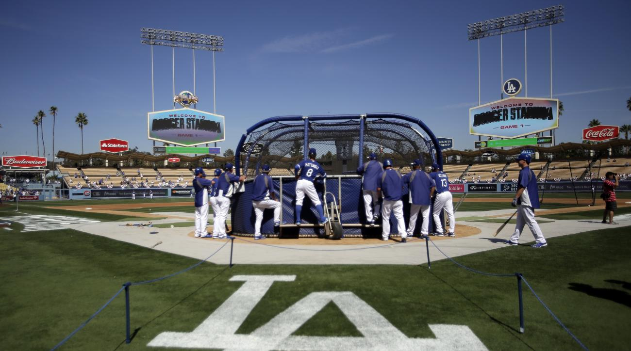FILE - In this Oct. 3, 2014, file photo, Los Angeles Dodgers players watch batting practice before Game 1 of baseball's NL Division Series against the St. Louis Cardinals in Los Angeles. The  Dodgers have been hit with a record luxury tax of nearly $43.6