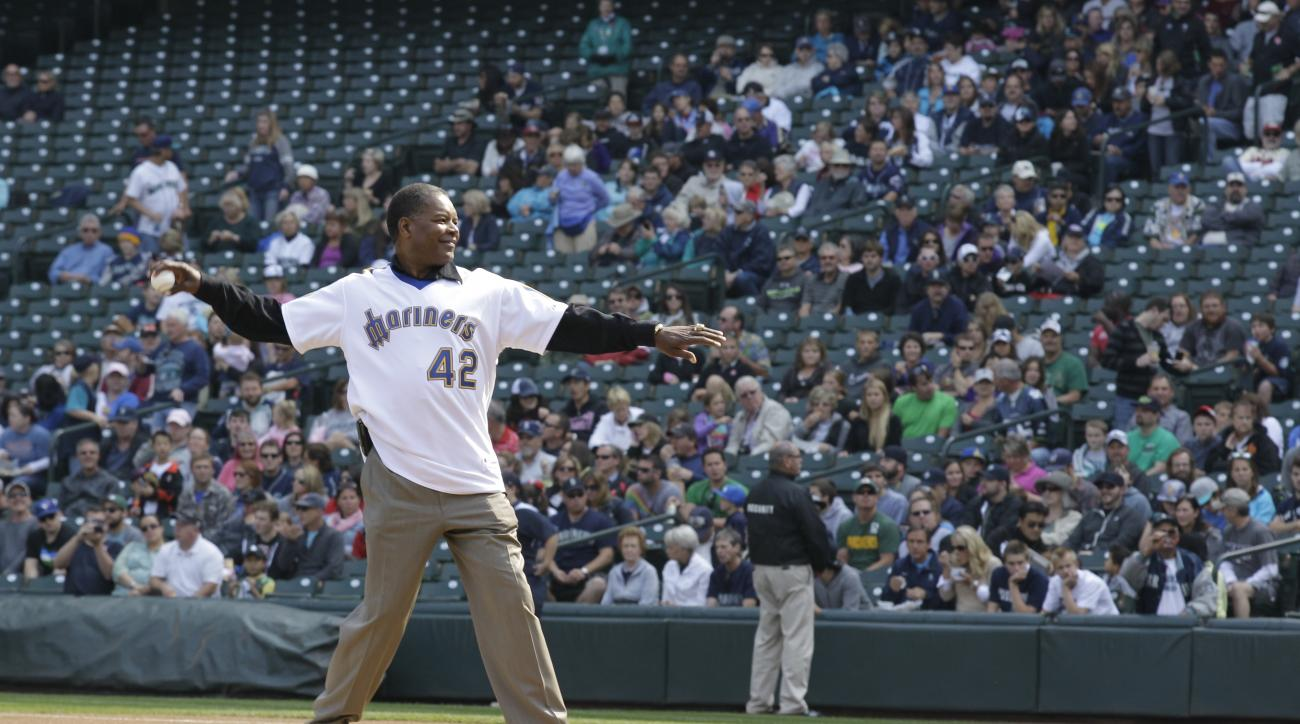 """Dave """"Hendu"""" Henderson, who played for the Seattle Mariners from 1981 to 1986, throws out the first pitch of a baseball game against the Texas Rangers, Sunday, Sept. 23, 2012, in Seattle. (AP Photo/Ted S. Warren)"""