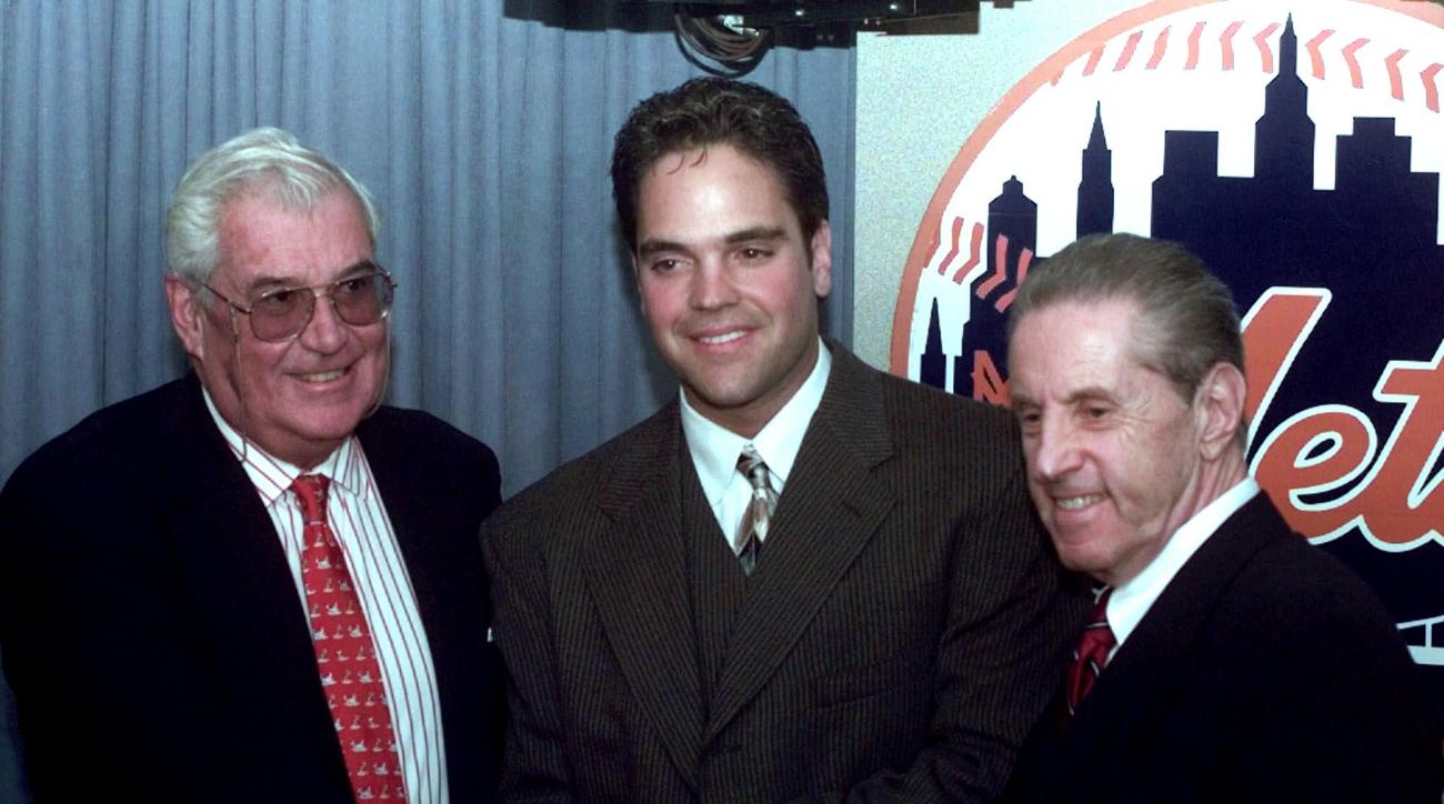 FILE - In this Oct. 26, 1996, file photo, New York Mets catcher Mike Piazza, center, smiles with Mets owners Nelson Doubleday, left, and Fred Wilpon, after the press conference about Piazza's record seven-year $91 million dollar contract with the Mets at