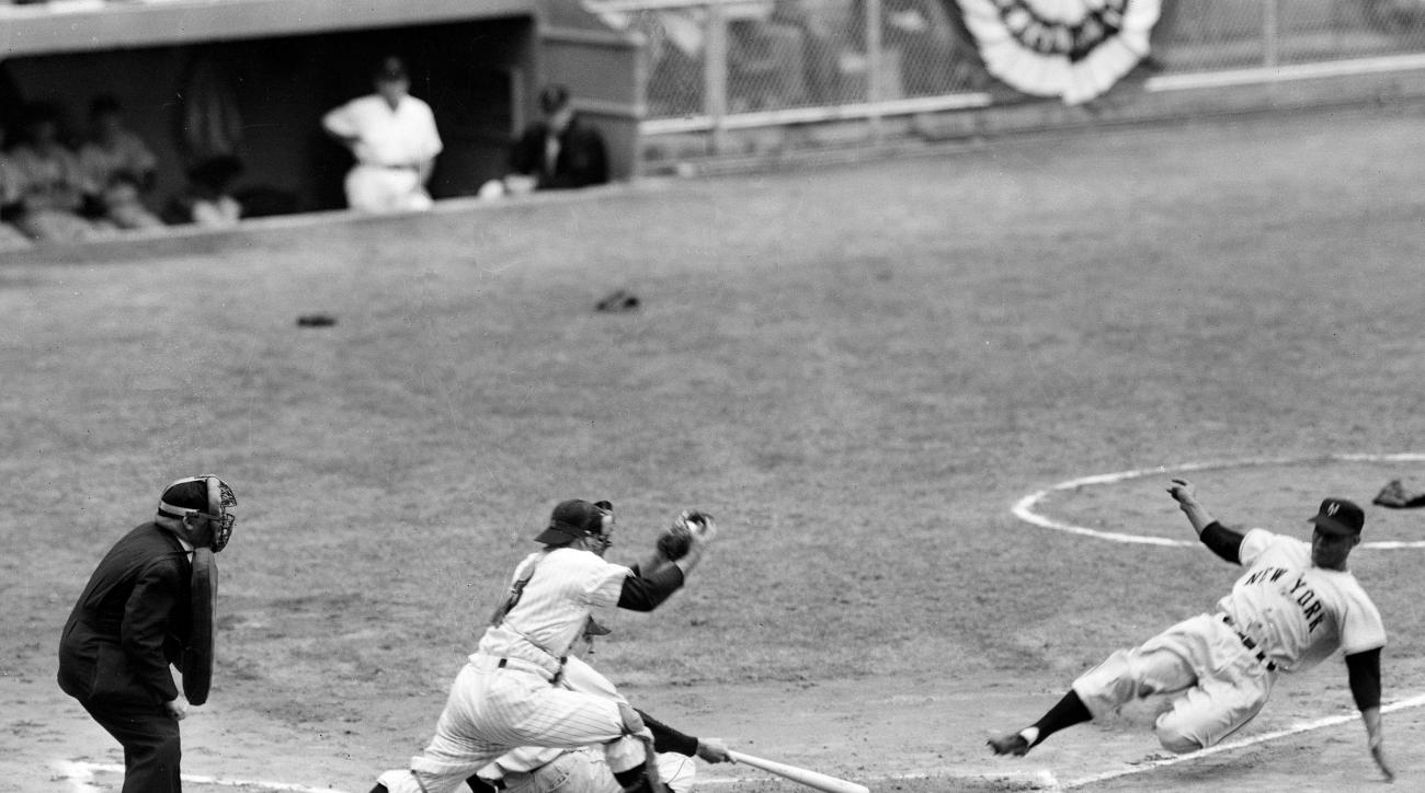 FILE - In this Oct. 4, 1951, file photo, New York Giants' Monte Irvin, right, successfully steals home as New York Yankees catcher Yogi Berra steps up to the plate with the ball in the first inning of game 1 in baseball's World Series at Yankee Stadium in