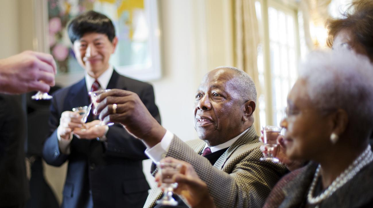 Hank Aaron, center, joins a toast with Consul General of Japan in Atlanta Takashi Shinozuka, rear, and Aaron's wife Billye, right, after being presented with the Order of the Rising Sun, Gold Rays with Rosette, by Shinozuka at his official residence, Thur
