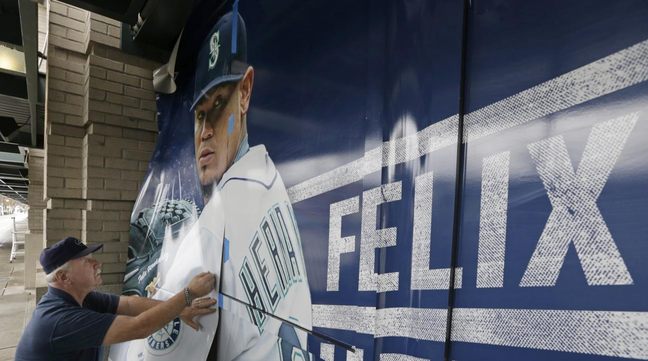 Craig Brookbush, of Rainier Industries, applies a new window display on the exterior of Safeco Field in Seattle featuring Seattle Mariners pitcher Felix Hernandez, Thursday, Jan. 28, 2016. Brookbush said that most of the player signs around the stadium wi