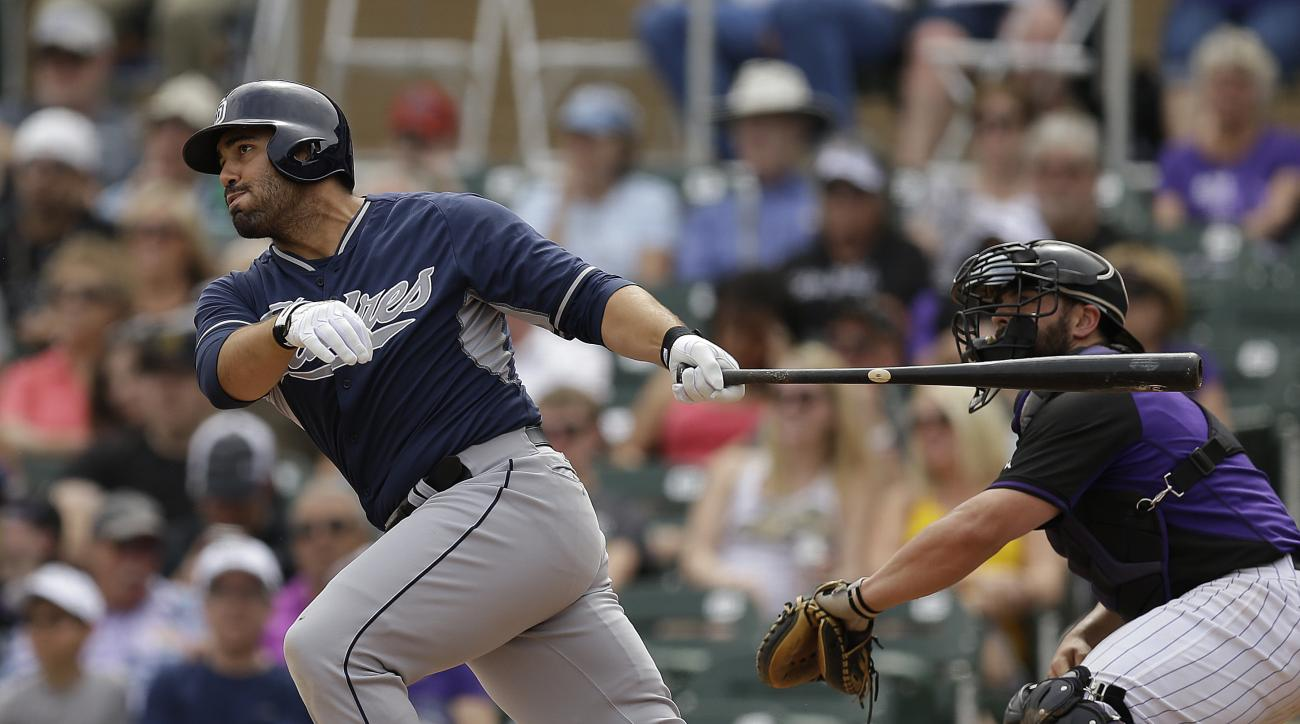 FILE - In this March 18, 2015, file photo, San Diego Padres' Carlos Quentin, left, follows through with a double in the second inning of a spring training exhibition baseball game against the Colorado Rockies in Scottsdale, Ariz. Quentin and the Minnesota