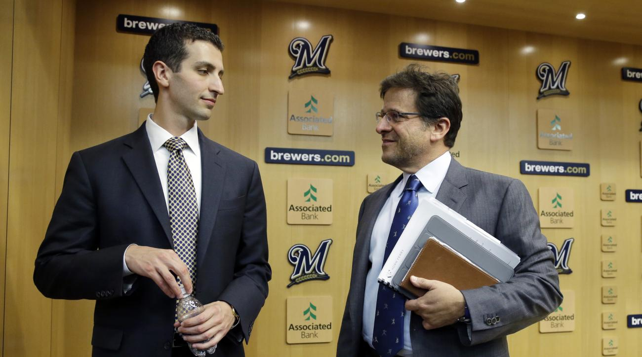 FILE - In this Sept. 21, 2015, file pjoto, Milwaukee Brewers general manager David Stearns,left, talks to owner Mark Attanasio at a news conference in Milwaukee. When Attanasio checks in with Stearns, he likes to test him like a fan about the team's lates