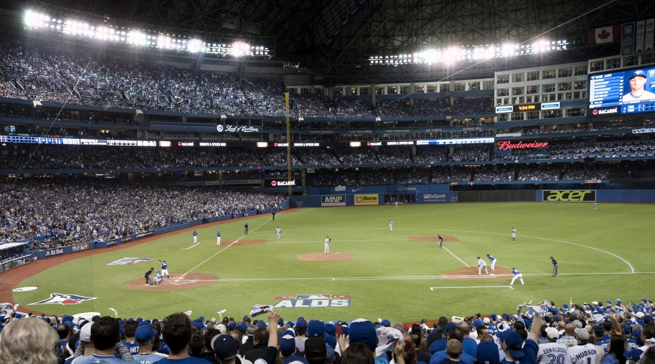 FILE - In this Oct. 9, 2015, file photo, the Toronto Blue Jays and the Texas Rangers play during the first inning of Game 2 of an AL division series in Toronto. The Blue Jays are installing a dirt infield at the Rogers Centre for the first time but say it