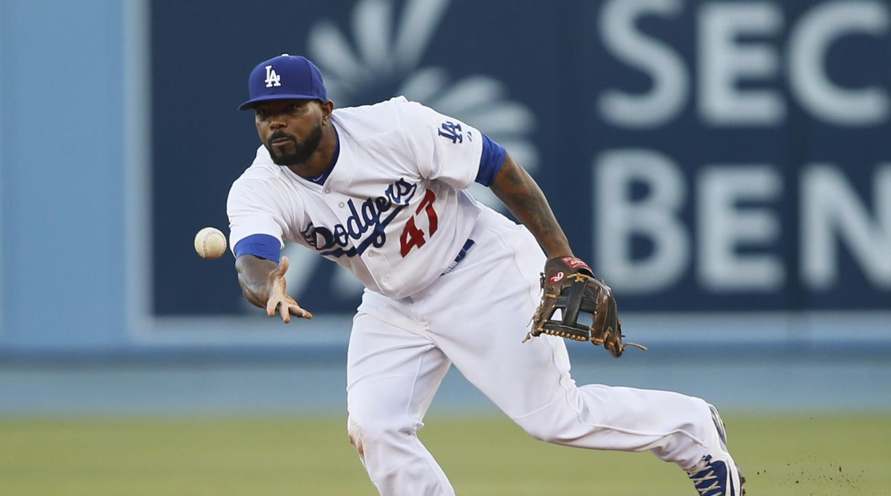 FILE - In this Saturday, July 11, 2015 file photo, Los Angeles Dodgers second baseman Howie Kendrick tosses the ball to force out Milwaukee Brewers' Gerardo Parra at second base as a part of a double play on a ground ball by Jonathan Lucroy during the fir
