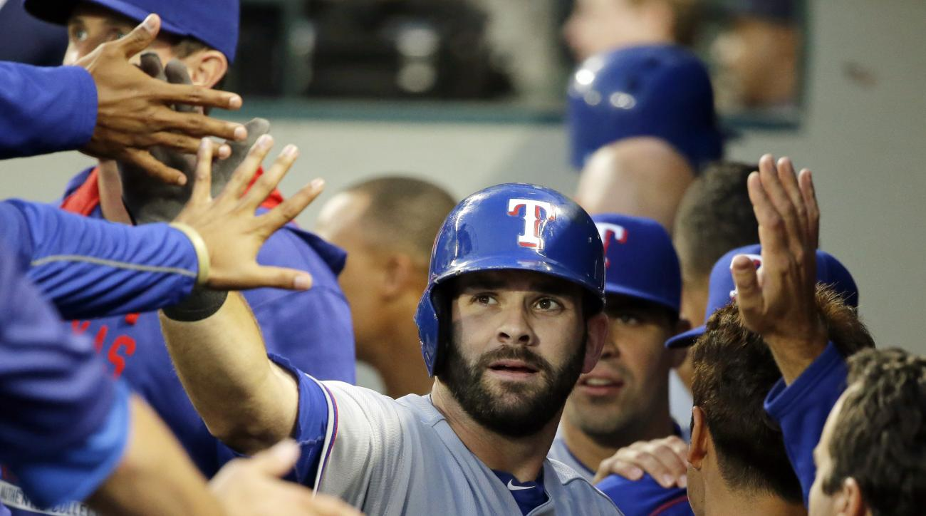 FILE - In this Sept. 8, 2015, file photo, Texas Rangers' Mitch Moreland, center, is greeted in the dugout after he hit a solo home run during the second inning of a baseball game against the Seattle Mariners, in Seattle. Moreland has agreed to a $5.7 mill