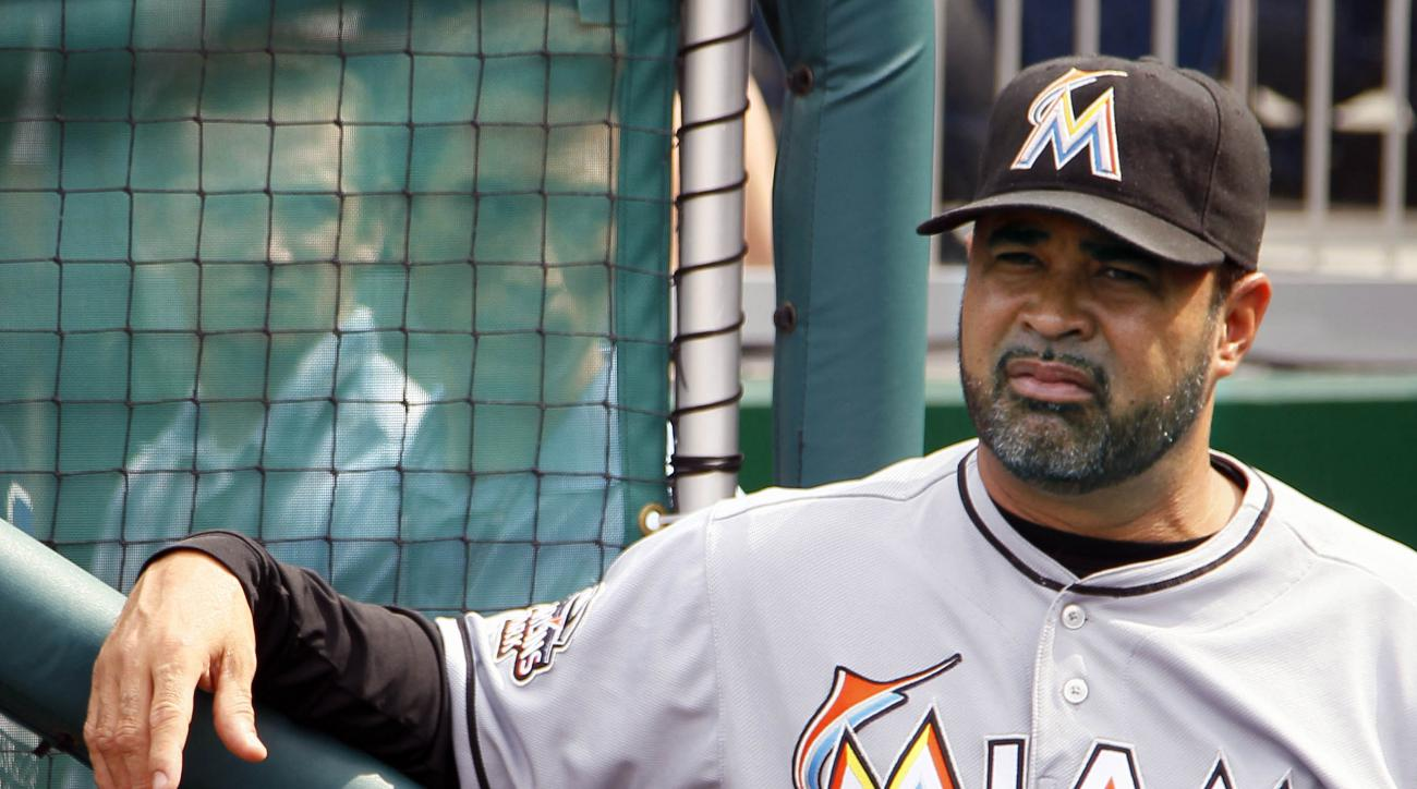 FILE - In this Friday, Aug. 3, 2012 file photo, Miami Marlins manager Ozzie Guillen waits in the dugout before the first baseball game of a doubleheader against the Washington Nationals in Washington. Ozzie Guillen, who led the Chicago White Sox to the 20