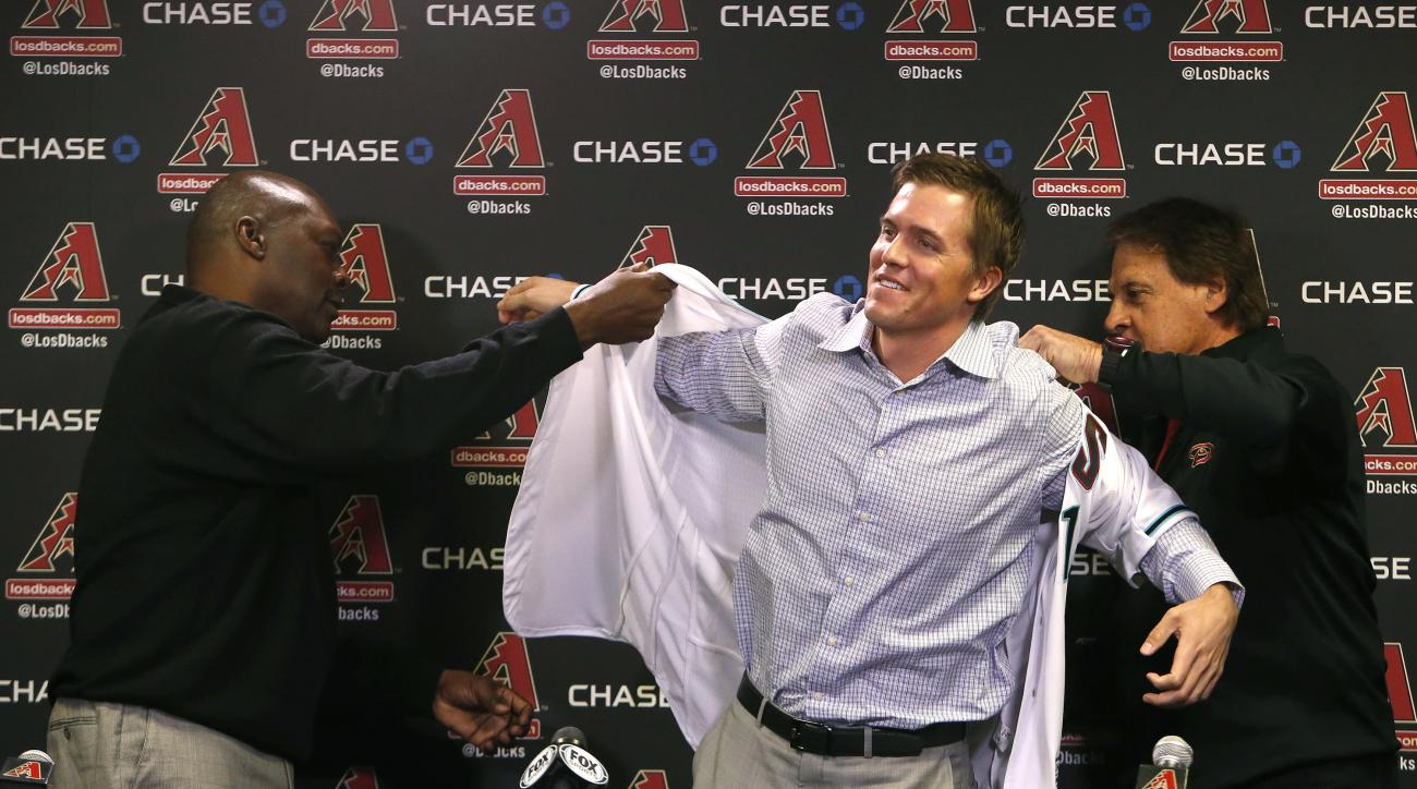 FILE - In this Dec. 11, 2015, file photo, Arizona Diamondbacks General Manager Dave Stewart, left, and Chief Baseball Officer Tony La Russa, right, introduce pitcher Zack Greinke to the media during a press conference, in Phoenix. Spring training is a tim