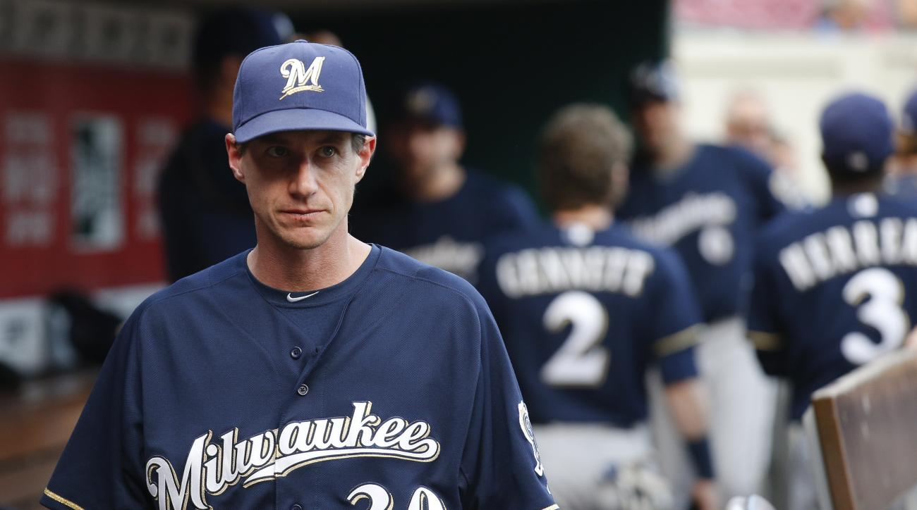FILE - In this Sept. 5, 2015, file photo, Milwaukee Brewers manager Craig Counsell walks through the dugout before the second game of a baseball doubleheader against the Cincinnati Reds in Cincinnati. The Brewers are rebuilding, and Counsell will start to