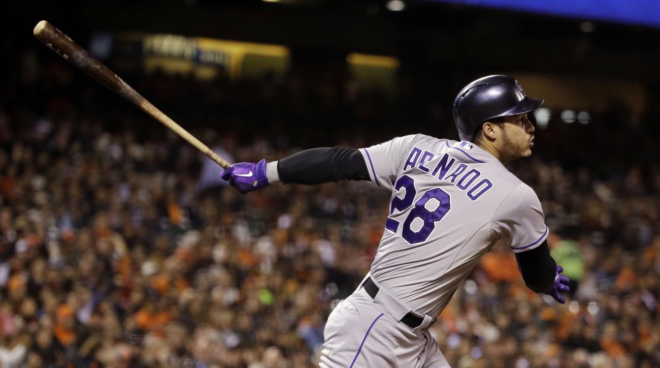 FILE - In this Oct. 2, 2015, file photo, Colorado Rockies' Nolan Arenado drives in two runs with a double against the San Francisco Giants during the third inning of a baseball game, in San Francisco. This is Arenado's team now and the All-Star third base