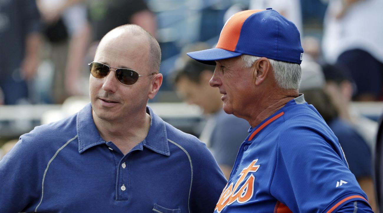 FILE - In this Wednesday, March 25, 2015 file photo, New York Yankees general manager Brian Cashman, left, talks to New York Mets manager Terry Collins before an exhibition baseball game in Tampa, Fla. For the first time in the four decades of baseball's