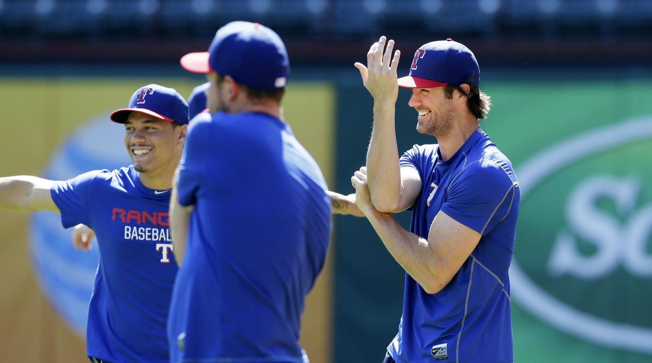 FILE - In this Tuesday, Oct. 6, 2015 file photo, Texas Ranges pitcher Cole Hamels, right, stretches with teammates during a baseball workout in Arlington, Texas. There will be a moment early in spring training when the Rangers gather as a group and put la