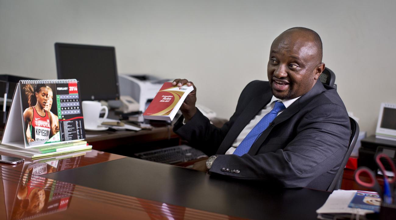 FILE---In this file photo taken Monday, Feb. 8, 2016, Athletics Kenya CEO Isaac Mwangi holds up a copy of the IAAF Competition Rules book, to illustrate his denial that Athletics Kenya would have the power to shave time off athletes' bans, during an inter