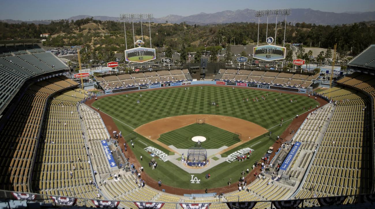 FILE - In this Oct. 3, 2014, file photo, the Los Angeles Dodgers and the St. Louis Cardinals gather on the field for batting practice at Dodger Stadium before Game 1 of baseball's NL Division Series in Los Angeles. The Los Angeles Dodgers have signed a mu