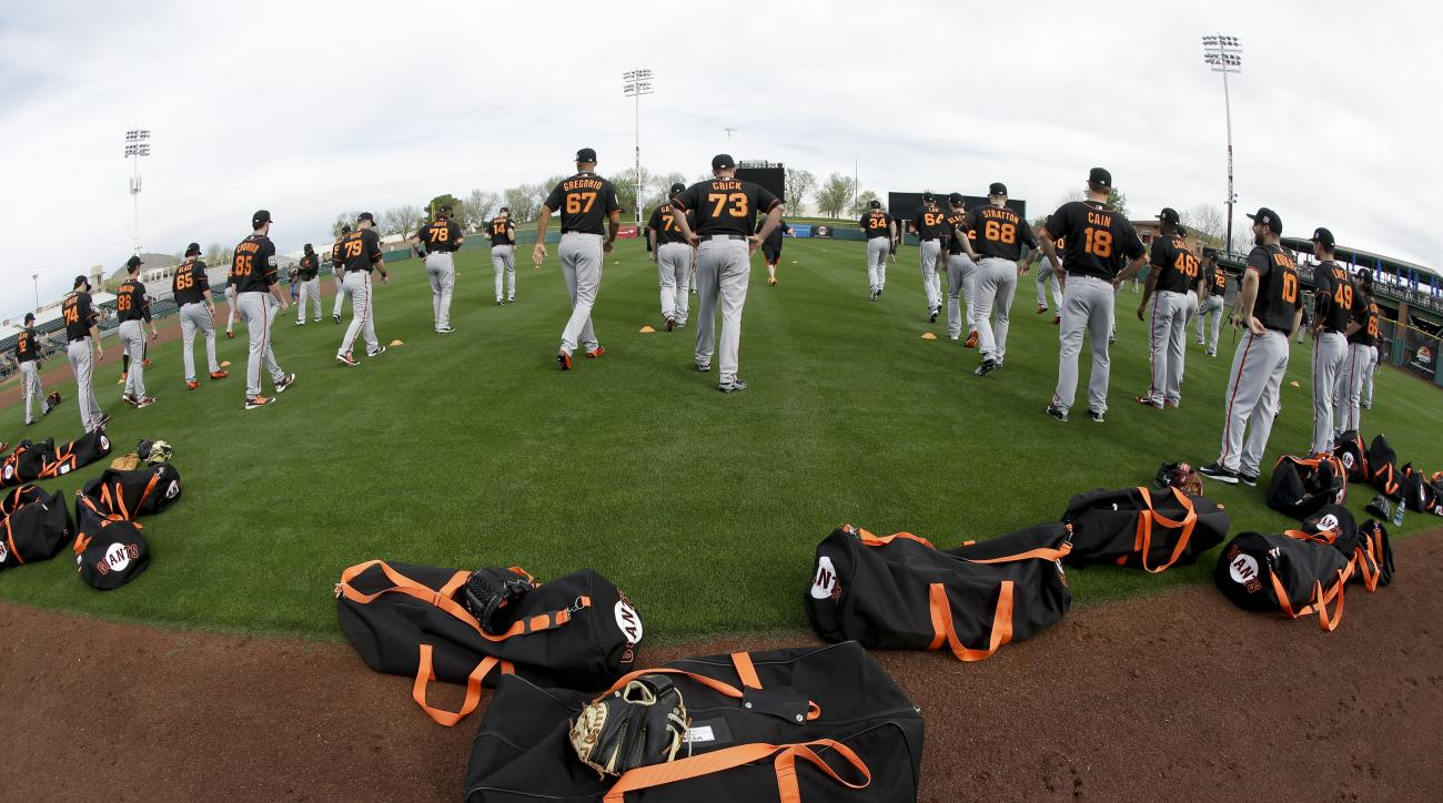 Members of the San Francisco Giants warm up before spring training baseball practice in Scottsdale, Ariz., Thursday, Feb. 18, 2016. (AP Photo/Chris Carlson)