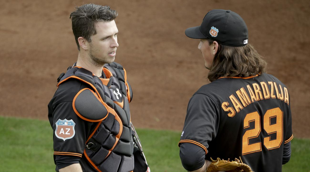 San Francisco Giants catcher Buster Posey, left, and starting pitcher Jeff Samardzija chat during practice before the spring baseball season in Scottsdale, Ariz., Thursday, Feb. 18, 2016. (AP Photo/Chris Carlson)