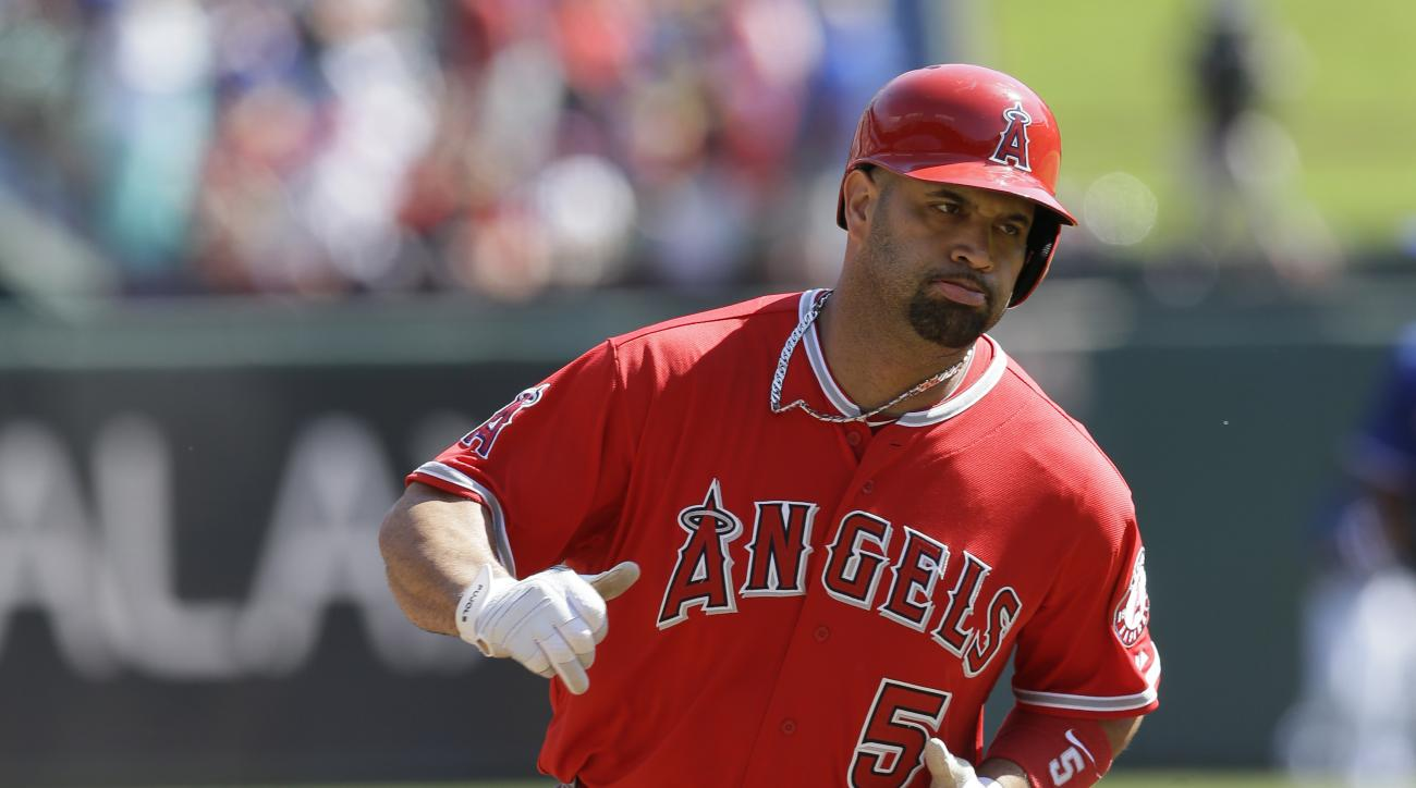 Los Angeles Angels Albert Pujols (5) runs the bases after hitting a two run homer during the first inning of a baseball game against the Texas Rangers in Arlington, Texas, Sunday, Oct. 4, 2015.  Mike Trout also scored on the play. (AP Photo/LM Otero)