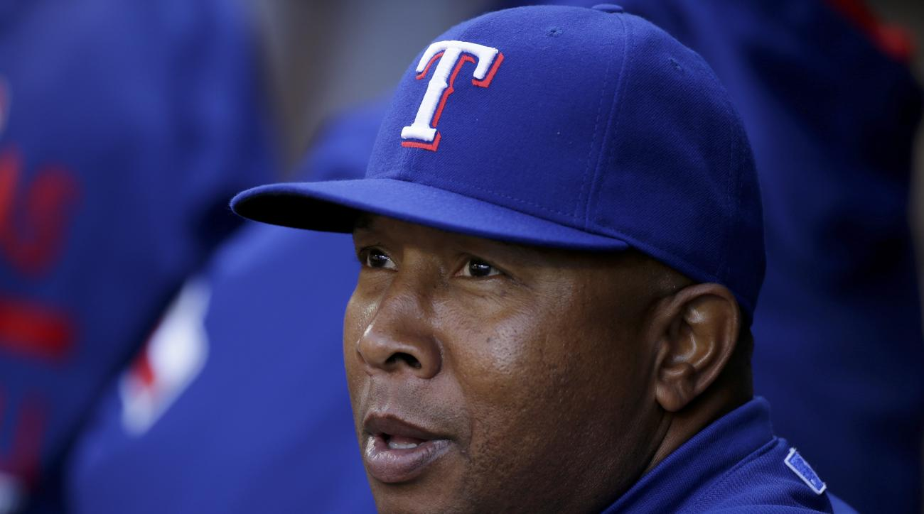FILE - In this April 18, 2015, file photo, Texas Rangers third base coach Tony Beasley stands in the dugout before the team's baseball game against the Seattle Mariners in Seattle. Beasley will undergo chemotherapy during spring training after being diagn