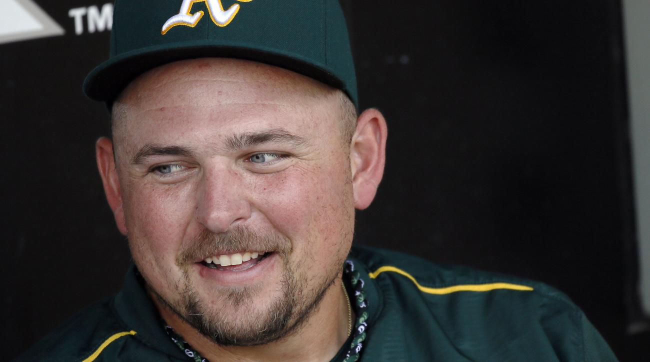 FILE - In this Sept. 17, 2015, file photo, Oakland Athletics designated hitter Billy Butler gives an interview in the dugout after a baseball game against the White Sox in Chicago.The 29-year-old Butler is confident his intense regimen all winter in Arizo