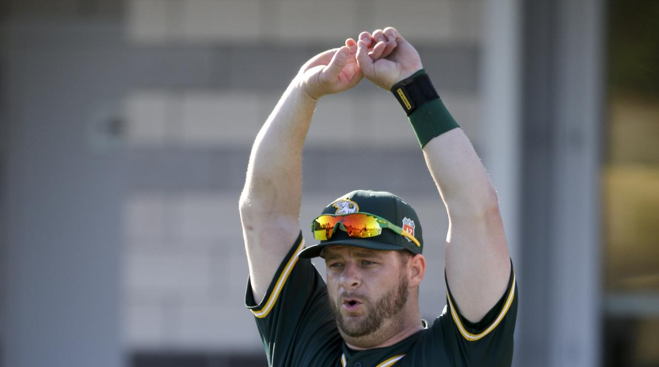 Oakland Athletics catcher Stephen Vogt warms up before spring training baseball practice in Mesa, Ariz., Sunday, Feb. 21, 2016. (AP Photo/Chris Carlson)