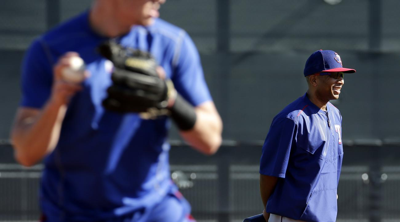 Texas Rangers third base coach Tony Beasley watches a drill during spring training baseball practice Sunday, Feb. 21, 2016, in Surprise, Ariz. (AP Photo/Charlie Riedel)