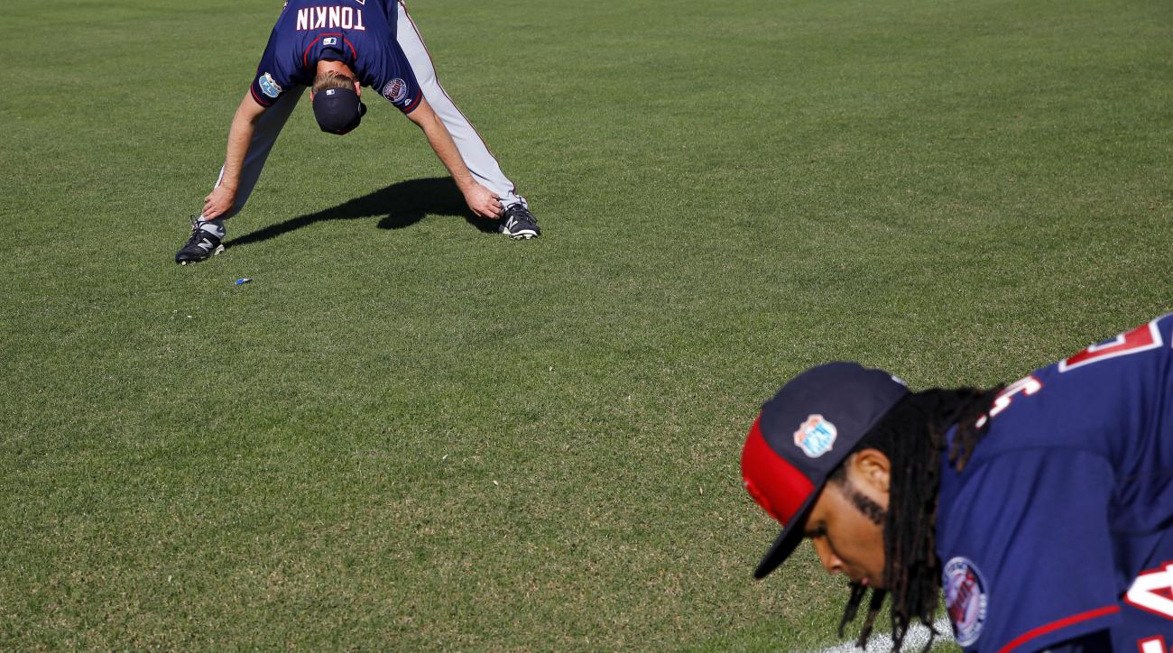 Minnesota Twins pitchers Michael Tonkin, left, and Ervin Santana stretch at the beginning of a spring training baseball workout in Fort Myers, Fla., Monday, Feb. 22, 2016. (AP Photo/Patrick Semansky)