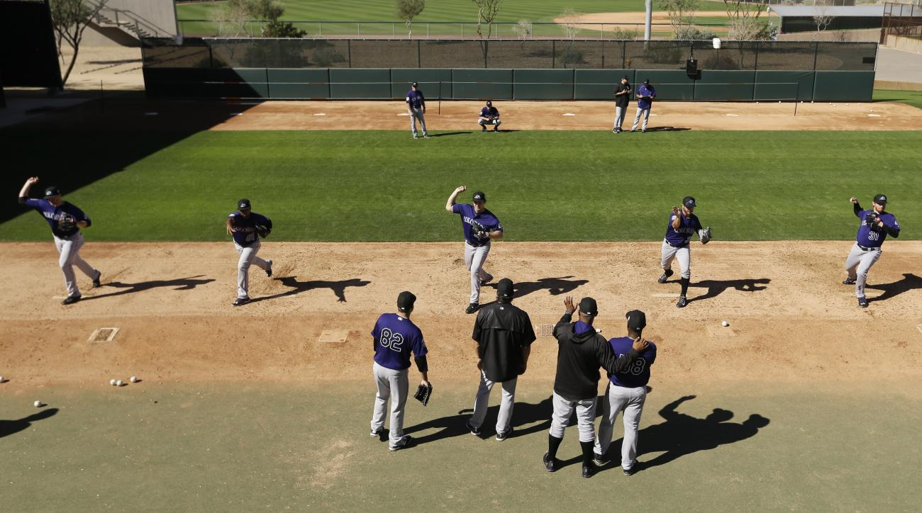 Members of the Colorado Rockies pitching staff work on drills during spring training baseball practice in Scottsdale, Ariz., Monday, Feb. 22, 2016. (AP Photo/Chris Carlson)