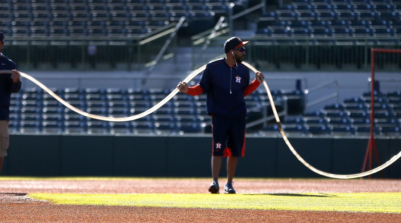 Osceola County Stadium groundskeepers support a hose as they water the infield on the main field during Houston Astros baseball spring training in Kissimmee, Fla., Monday, Feb. 22, 2016. (Karen Warren/Houston Chronicle via AP) MANDATORY CREDIT