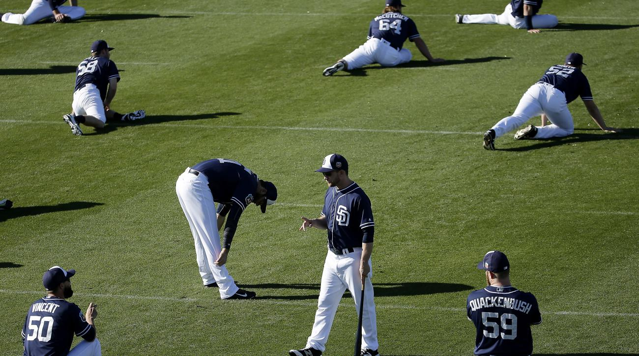 San Diego Padres manager Andy Green, center, holds a bat while talking to players as they stretch before spring training baseball practice Monday, Feb. 22, 2016, in Peoria, Ariz. (AP Photo/Charlie Riedel)