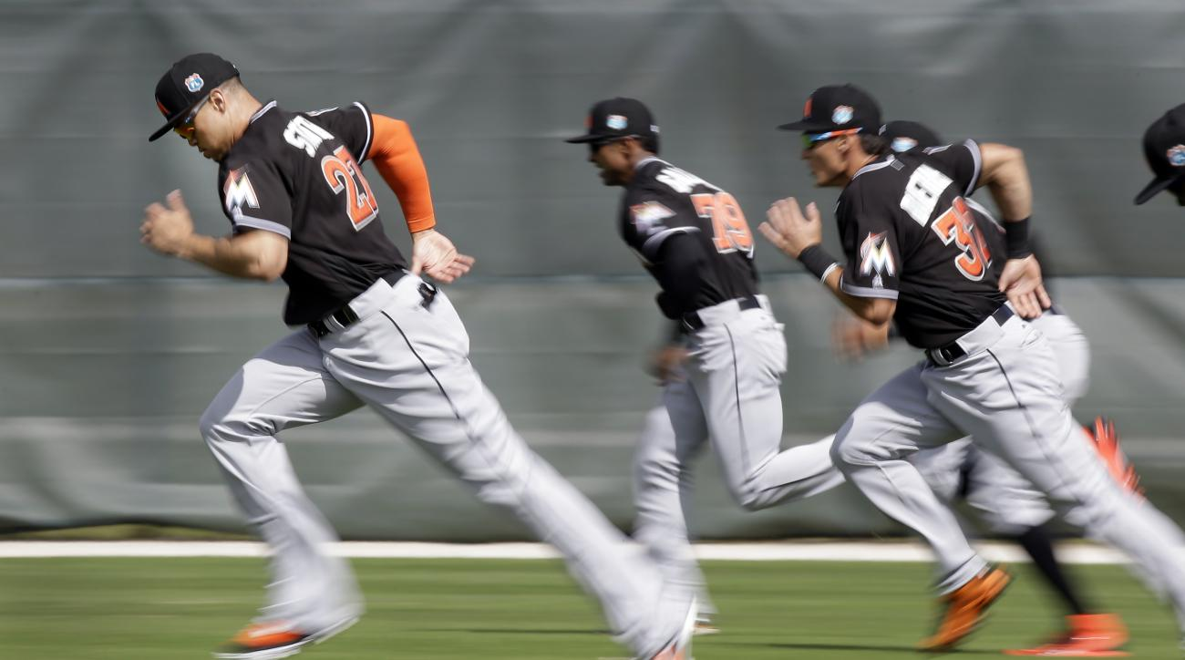 In this image taken with a slow shutter speed, Miami Marlins' Giancarlo Stanton, left, leads his teammates as they run sprints at the start of spring training baseball practice Tuesday, Feb. 23, 2016, in Jupiter, Fla. (AP Photo/Jeff Roberson)