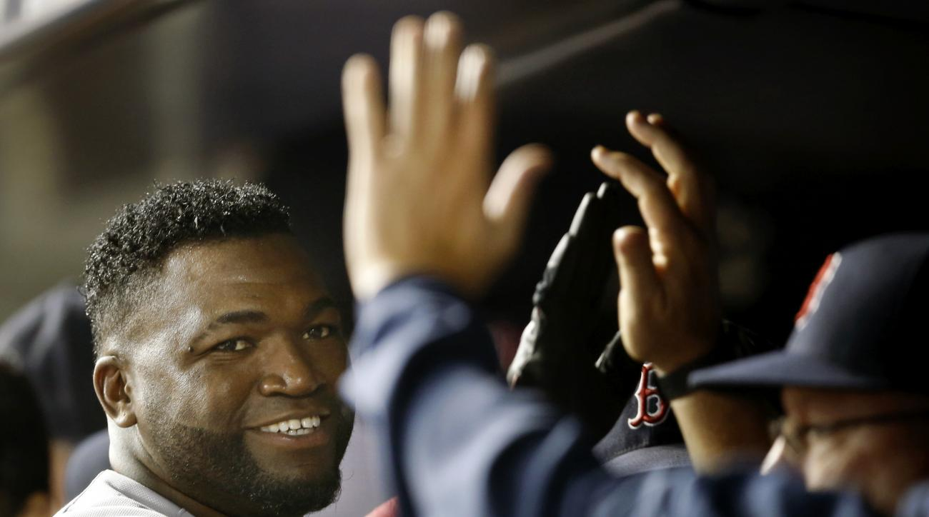 FILE - In this Sept. 29, 2015, file photo, Boston Red Sox's David Ortiz, left, is greeted by teammates in the dugout after scoring on Brock Holt's double in the first inning of a baseball game against the New York Yankees in New York. Ortiz hopes his 20th