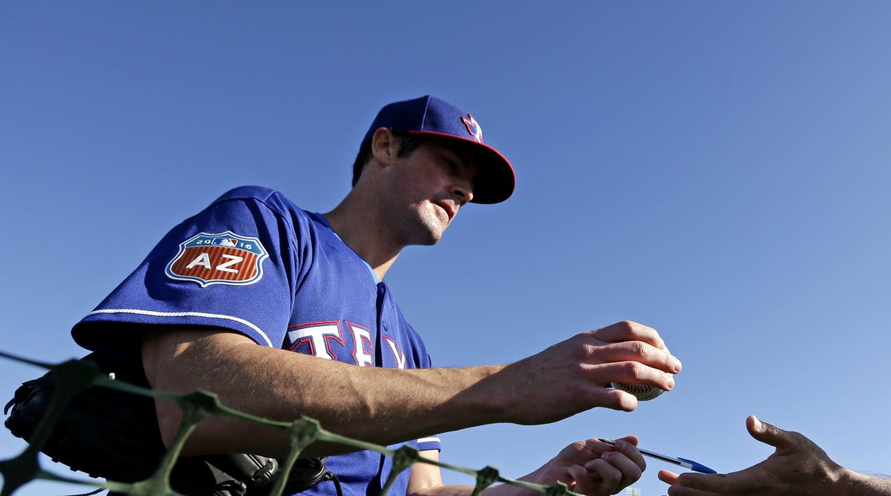 FILE - In this Feb. 21, 2016, file photo, Texas Rangers pitcher Cole Hamels signs autographs during spring training baseball practice, in Surprise, Ariz. Cole Hamels struck out trying to see last year's Victoria's Secret Fashion Show, and he's suing a Lon