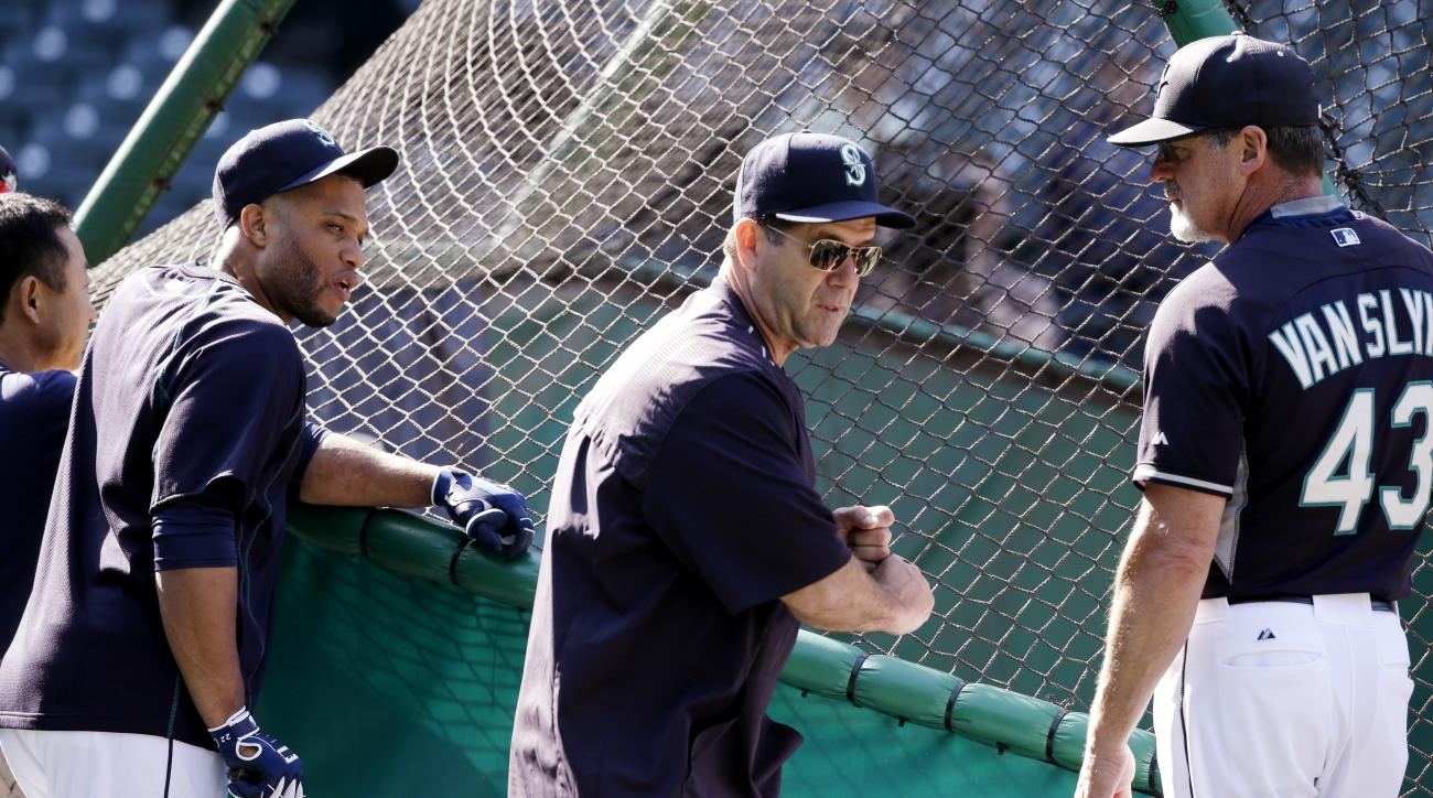 FILE - In this June 20, 2015, file photo, The Seattle Mariners' new hitting coach, Edgar Martinez, center, stands with assistant hitting coach Andy Van Slyke (43) and Robinson Cano outside the batting cage before the Mariners' baseball game against the Ho