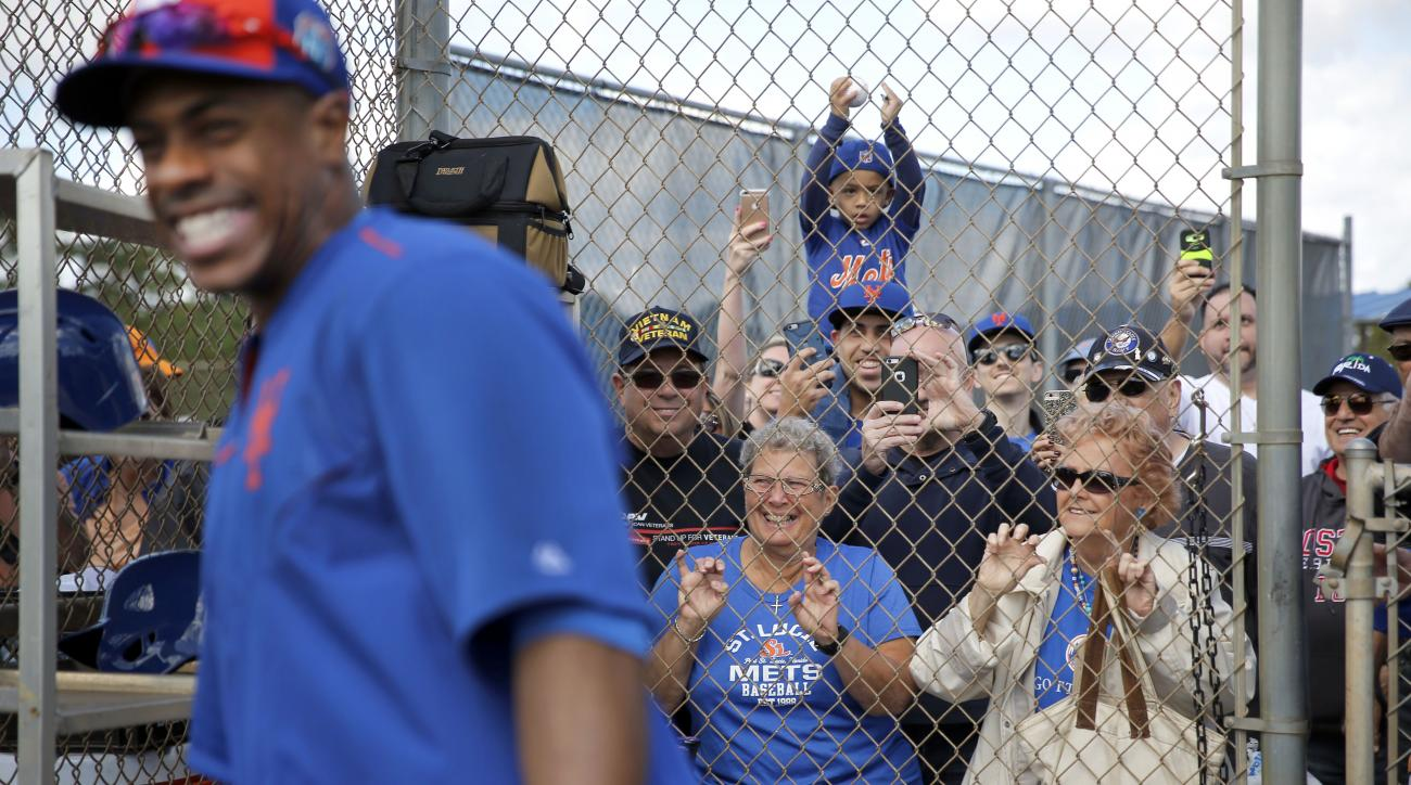 New York Mets' Curtis Granderson, left, smiles as he walks away after talking with fans during spring training baseball practice Friday, Feb. 26, 2016, in Port St. Lucie, Fla. (AP Photo/Jeff Roberson)