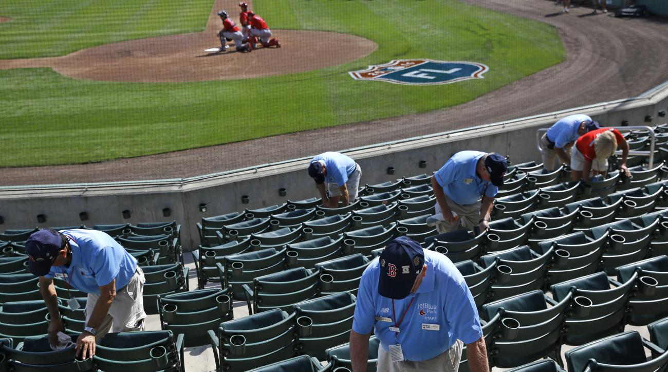 Ushers clean seats before a spring training baseball game between the Minnesota Twins and the Boston Red Sox in Fort Myers, Fla., Wednesday, March 2, 2016. (AP Photo/Patrick Semansky)