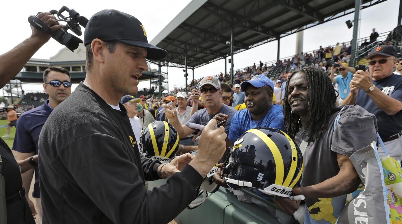 Michigan head football coach Jim Harbaugh signs autographs before a spring training baseball game between the Pittsburgh Pirates and the Detroit Tigers Wednesday, March 2, 2016, in Bradenton, Fla. Harbaugh coached first base for the Tigers. (AP Photo/Chri