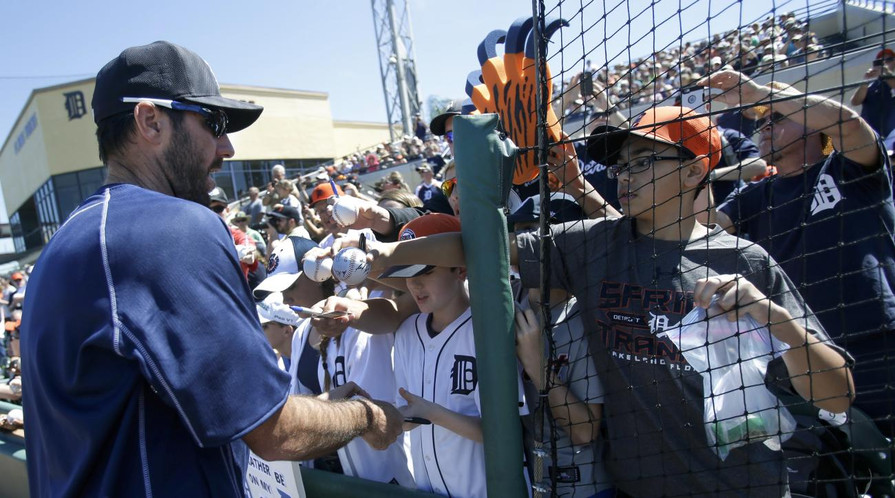 Detroit Tigers starting pitcher Justin Verlander, left, signs autographs for fans before a spring training baseball game against the Miami Marlins, Sunday, March 6, 2016, in Lakeland, Fla. (AP Photo/John Raoux)