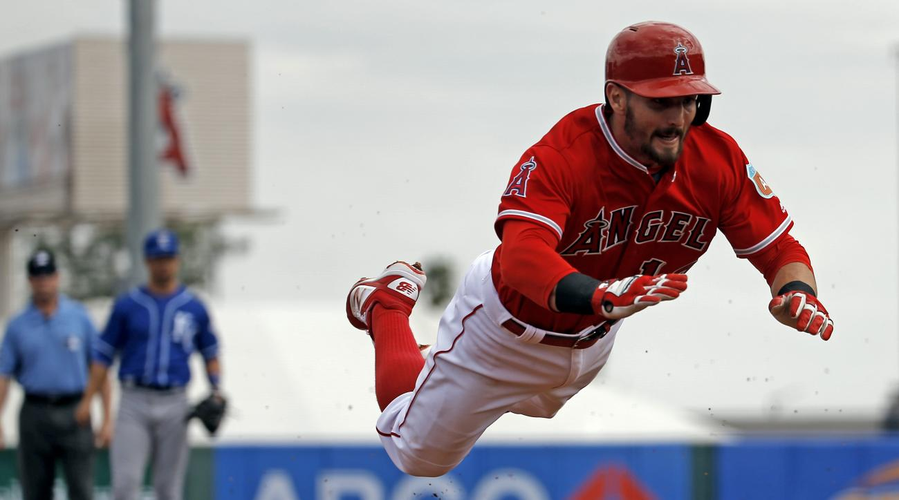Los Angeles Angels' Johnny Giavotella makes a head-first dive for a triple during the second inning of a spring training baseball game against the Kansas City Royals, Sunday, March 6, 2016, in Tempe, Ariz. (AP Photo/Morry Gash)
