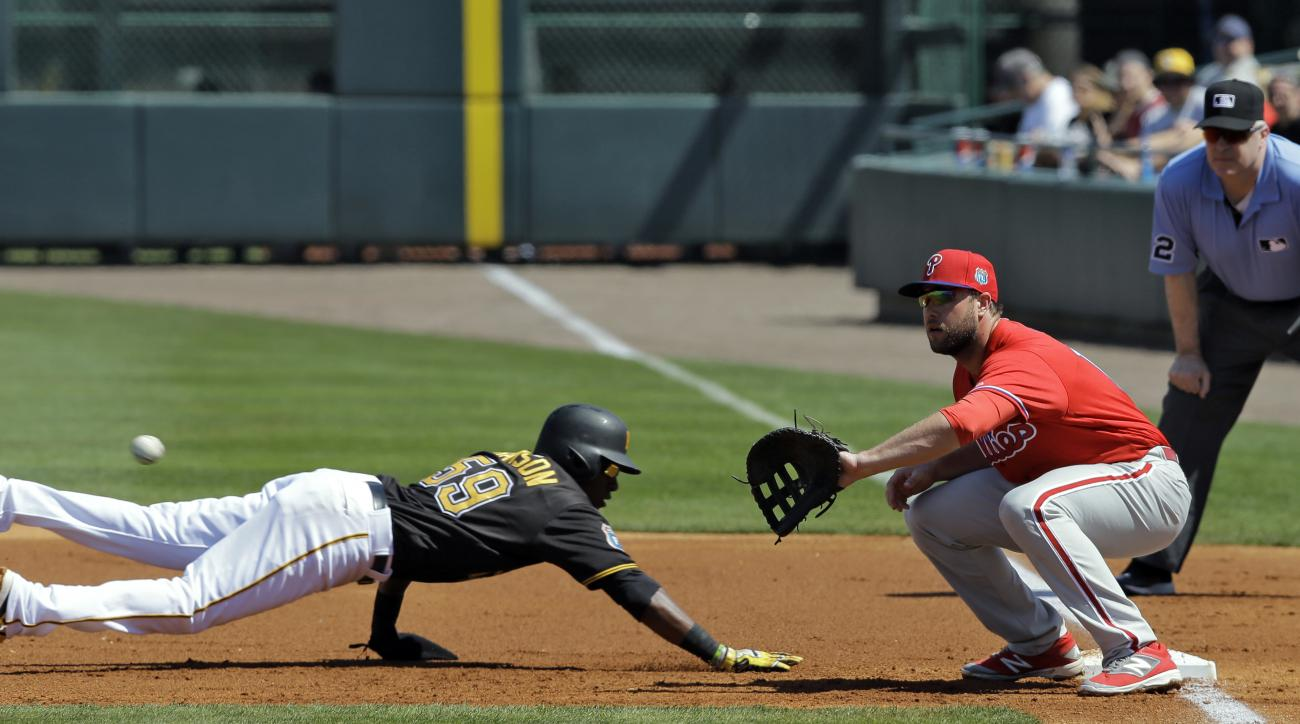 Pittsburgh Pirates' Alen Hanson (59) dives back ahead of the throw to Philadelphia Phillies first baseman Darin Ruf during the first inning of a spring training baseball game Monday, March 7, 2016, in Tampa, Fla. Looking on is umpire Bill Welke. (AP Photo
