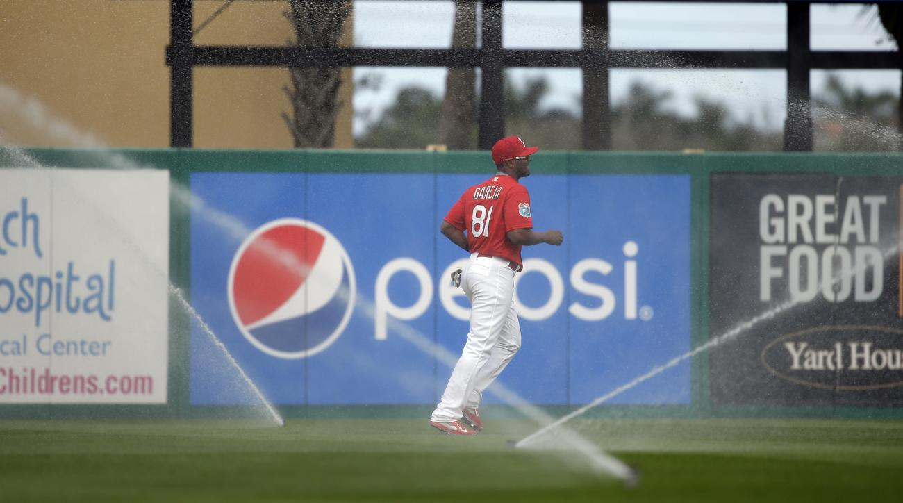 St. Louis Cardinals left fielder Anthony Garcia jogs away after automatic sprinklers came on unexpectedly during the sixth inning of an exhibition spring training baseball game against the New York Mets Monday, March 7, 2016, in Jupiter, Fla. (AP Photo/Je