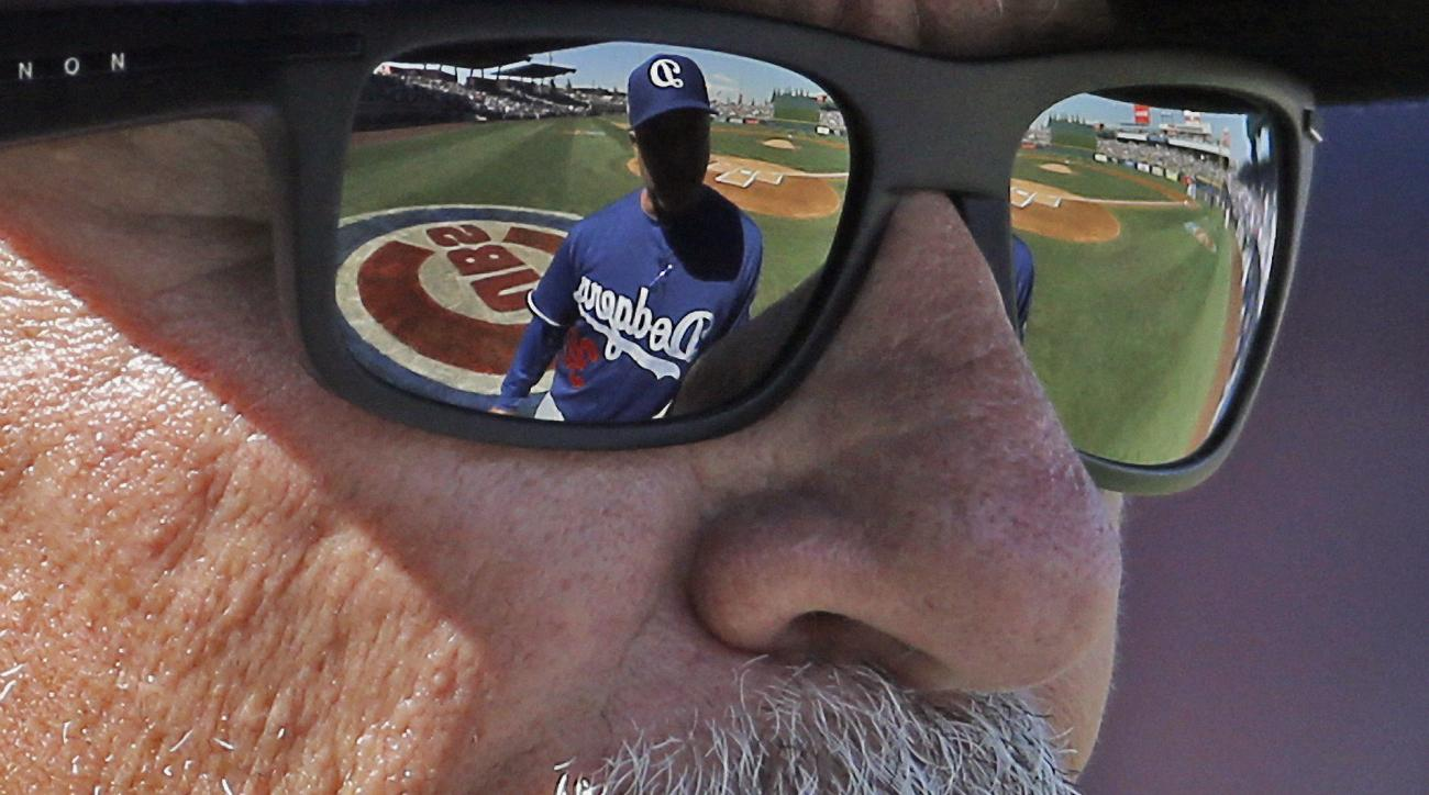 Los Angeles Dodgers manager Dave Roberts is reflected in the sunglasses of Chicago Cubs manager Joe Maddon as they talk before a spring training baseball game, Tuesday, March 8, 2016, in Mesa, Ariz. (AP Photo/Morry Gash)