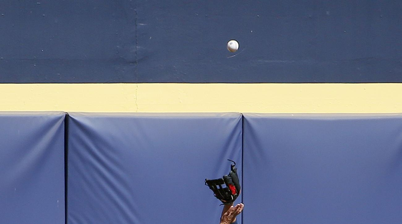 San Diego Padres' Jon Jay in unable to get to a home run ball hit by Arizona Diamondbacks' Peter O'Brien during the second inning of a spring training baseball game, Tuesday, March 8, 2016, in Peoria, Ariz. (AP Photo/Ross D. Franklin)