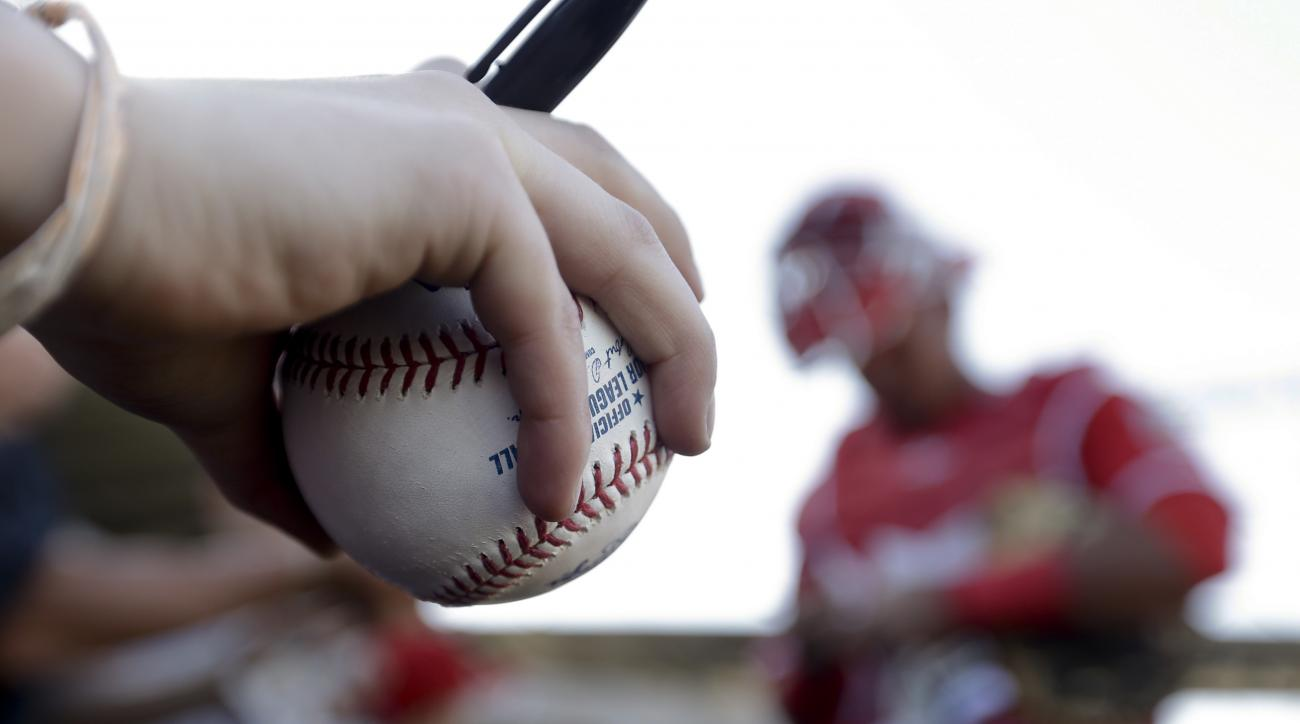 A fan waits for an autograph from Los Angeles Angels catcher Carlos Perez before the Angels' spring baseball game against the Arizona Diamondbacks in Scottsdale, Ariz., Tuesday, March 8, 2016. (AP Photo/Chris Carlson)