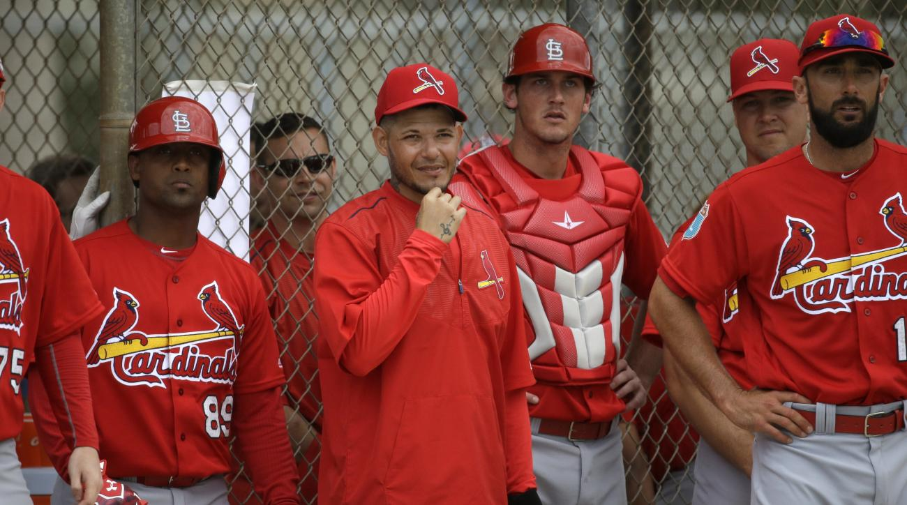 FILE - In this  Feb. 29, 2016 file photo, St. Louis Cardinals catcher Yadier Molina, center, watches from the dugout during a spring training intra-squad baseball game, in Jupiter, Fla. Molina is set to make his spring training debut behind the plate, wit