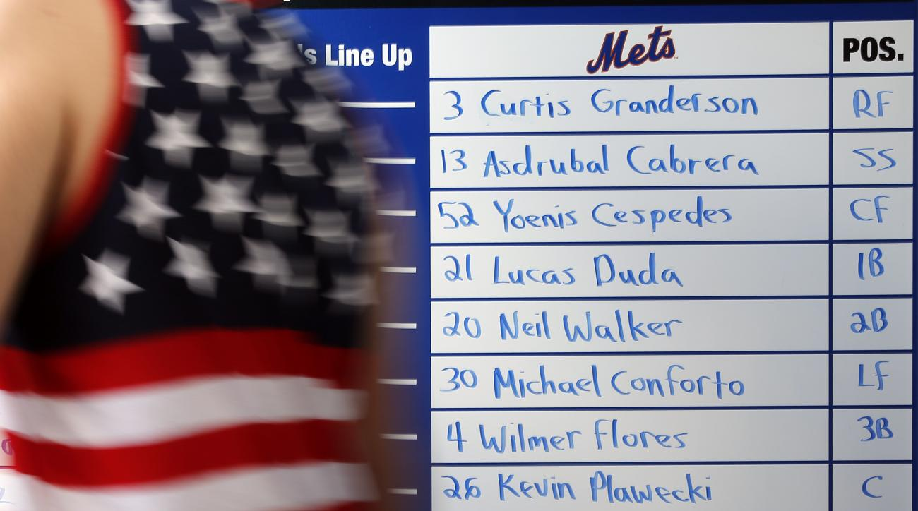 A fan walks past the New York Mets line up written on a board in a stadium entrance before the start of an exhibition spring training baseball game between the St. Louis Cardinals and the New York Mets Thursday, March 10, 2016, in Port St. Lucie, Fla. (AP