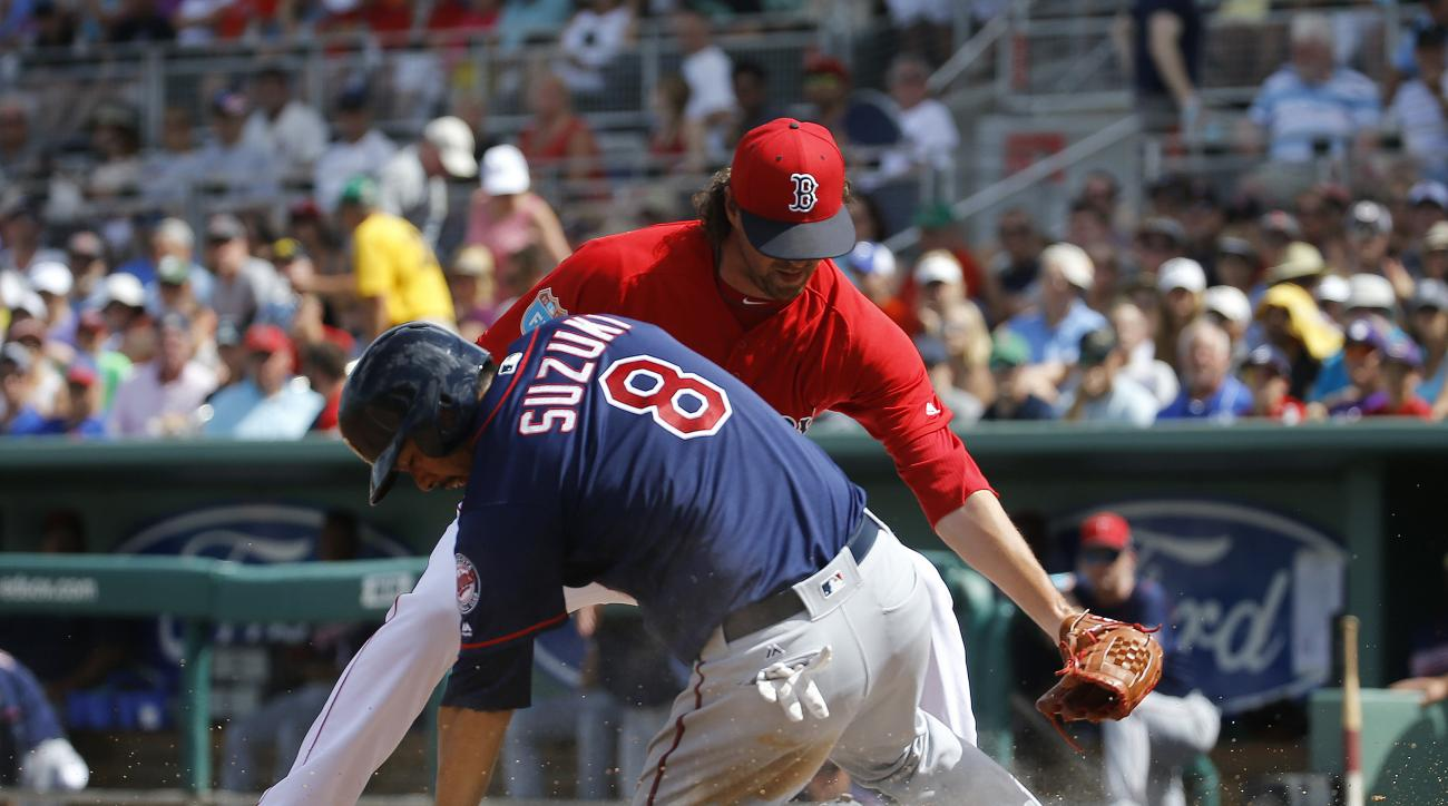 Minnesota Twins' Kurt Suzuki (8) slides over home plate for a run in front of Boston Red Sox relief pitcher Heath Hembree after a wild pitch in the fourth inning of a spring training baseball game in Fort Myers, Fla., Thursday, March 10, 2016. (AP Photo/P