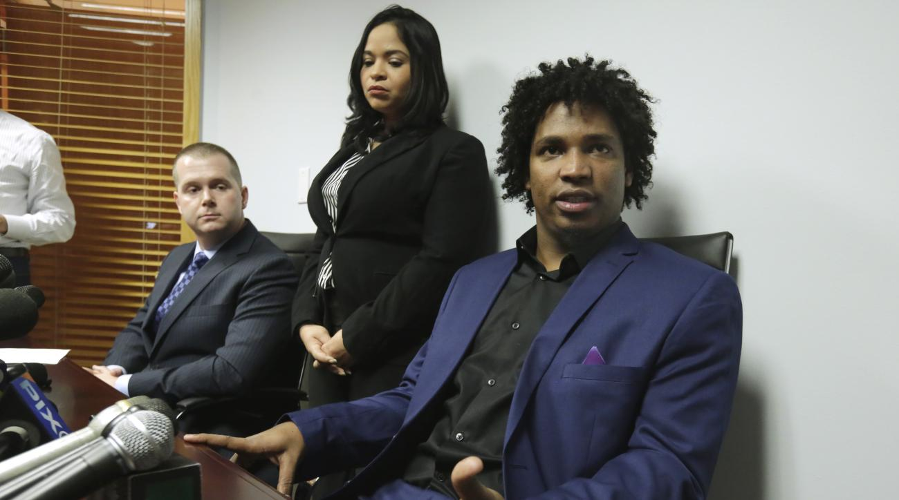 Former New York Mets pitcher Jenrry Mejia, right, addresses a news conference at the office of his attorney Vincent Peter White, left, in the Queens borough of New York, Friday, March 11, 2016. An interpreter is at center.  Suspended for life by Major Lea