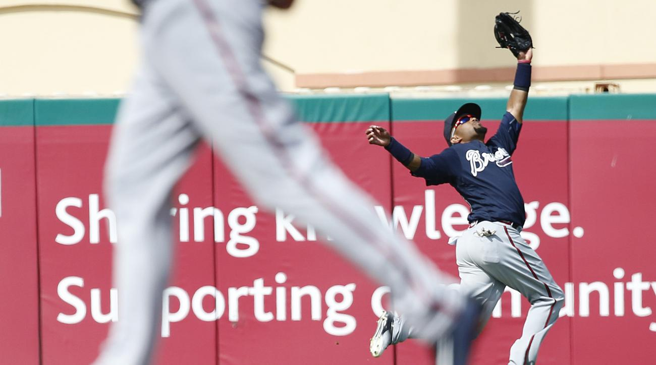 Atlanta Braves' second baseman Emilio Bonifacio, reaches for the fly ball throws during the sixth inning of an exhibition spring training baseball game against the St. Louis Cardinals, Friday, March 11, 2016, in Jupiter, Fla. (AP Photo/Brynn Anderson)