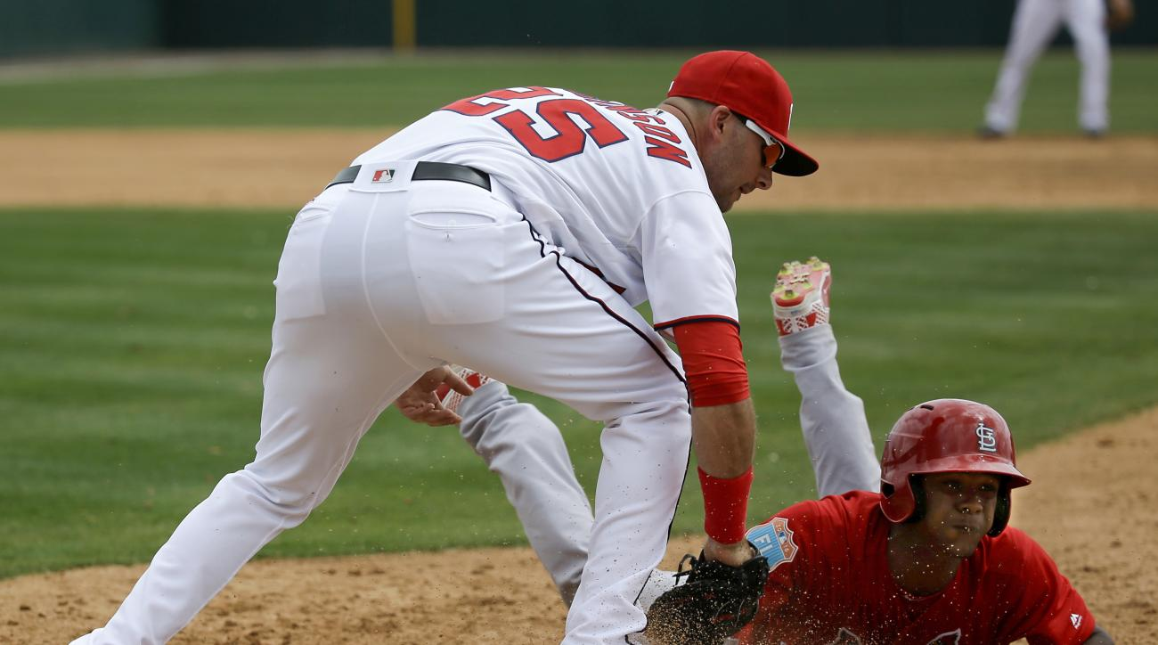 St. Louis Cardinals Magneuris Sierra, right, slides safely back to first base as Washington Nationals first baseman Clint Robinson, left, applies the tag in the third inning of a spring training baseball game, Sunday, March 13, 2016, in Viera, Fla. (AP Ph
